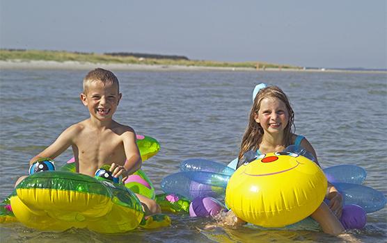 To barn på hvert sitt badedyr i vannet ved stranden