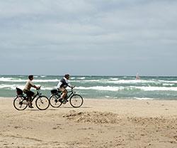Stel van middelbare leeftijd fietst langs de Noordzee