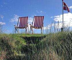 Rood-witte ligstoelen op een duin met de Deense vlag op de achtergrond