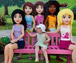Meisje op roze bankje omgeven door poppen gemaakt van LEGO