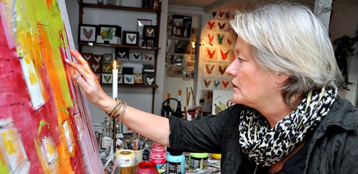Kvinde arbejder på et stort maleri i et galleri