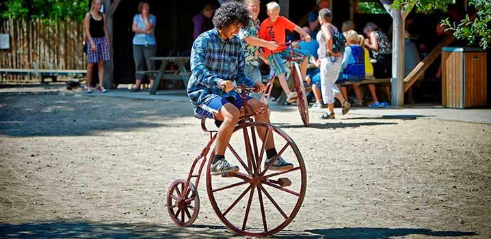 Kinder auf altmodischen Fahrrädern im Freilichtmuseum Hjerl Hede / Hjerl Hede