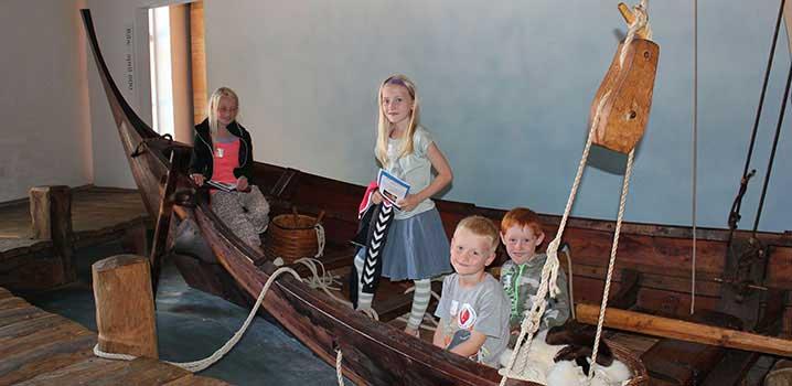 Spielende Kinder im Wikingerschiff des Museums / Museet Ribes Vikinger
