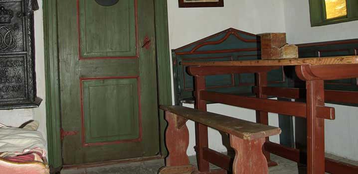 Museumsstue med gammel, håndlavet barneseng / Ølgod Museum