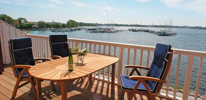 Tre stole omkring et bord på en altan med udsigt over en lystbådehavn.