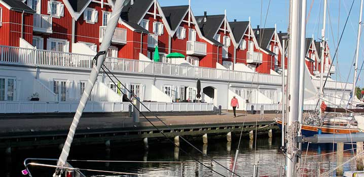 Røde og hvide ferielejligheder på stribe ud til lystbådehavn med både i.