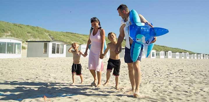 Mutter und Vater gehen Hand in Hand mit deren beiden Jungs am Strand. Vater hat ein großes Badetier unter dem Arm