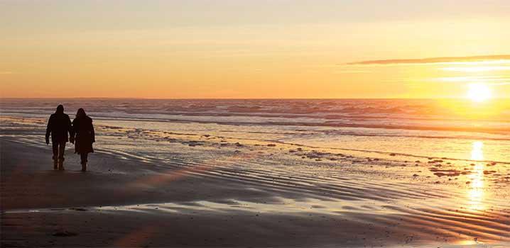Paare genießen den Sonnenuntergang am Wattenmeer