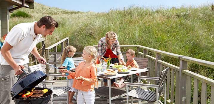 Familie auf der Terrasse bei einem Ferienhaus. Der Vater händigt seiner Tochter etwas vom Grill, während der Rest der Familie im Hintergrund am Tisch sitzt