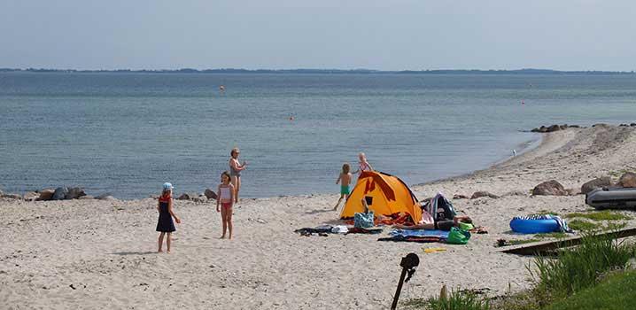 Spielende Kinder am Strand von Hasmark an einem schönen Sommertag