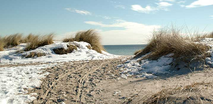 Nedgang til stranden mellem klitter med sol og sne