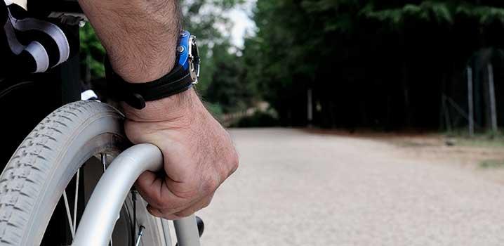 Mann im Rollstuhl auf einem Kiesweg