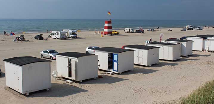 Die charakteristischen weißen Badehäuser und Rettungsschwimmerturm  am Strand von Løkken