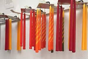 Kaarsen hangen op een rij, klaar om verkocht te worden