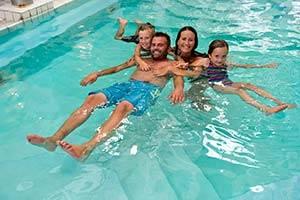 Familie svømmer i bassin