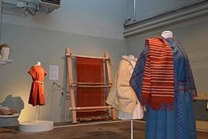 Vævet klædedragt i blå og røde farver