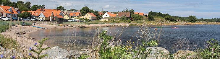 Den lille, hyggelige badestrand i Årsdale er omgivet af klipper