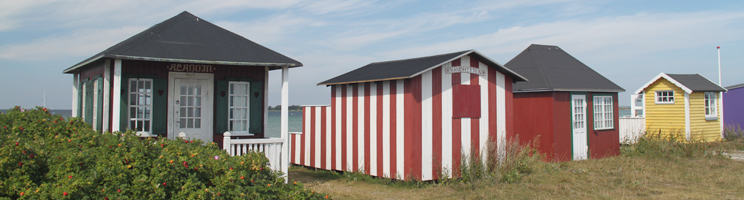 Idyllic and colourful beach huts along the bathing beach in Ærøskøbing