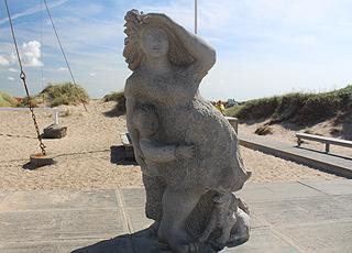 Skulptur af en kvinde, der spejder ud over havet, ved stranden i Agger