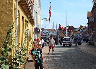 Brostensbelagt gade med smukke, gamle huse ved havnen i Allinge