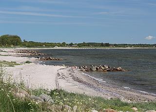Sandstrand mit kleinen Buchten und seichtem Badewasser im Ferienhausgebiet Amtoft