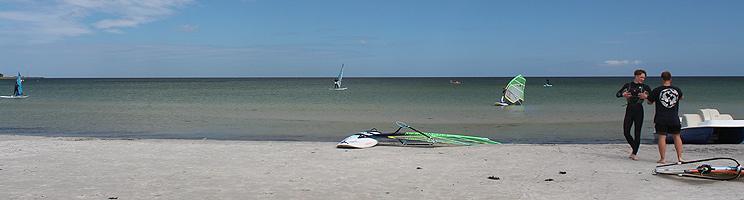 Surfere på den brede sandstrand med lavt og klart badevand i Balka