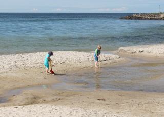 Børn leger i vandkanten i sommerhusområdet Boderne