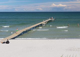 Badegäste auf dem Badesteg und im Wasser am Strand im Urlaubsgebiet Bratten