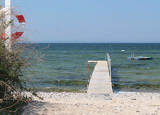 Aussicht über den Badesteg und das klare Badewasser im Urlaubsgebiet Bro Strand