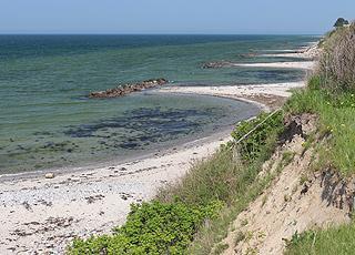 Steile Hänge hinter den Buchten des Strandes am östlichen Ende von Bro Strand