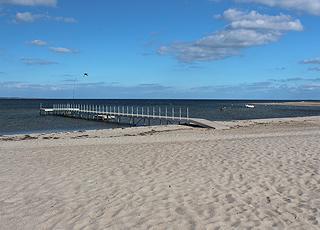 Lang badebro ved den brede sandstrand i ferieområdet Diernæs