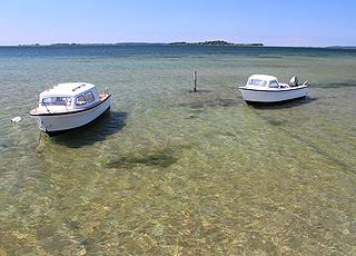 Små både på det klare vand i ferieområdet Falsled