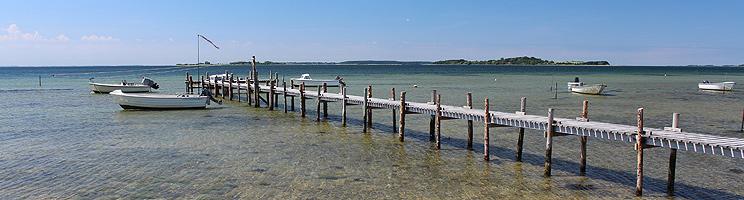 Lang badebro i det klare vand ved stranden i sommerhusområdet Falsled