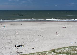 En sommerdag med badegæster på den brede sandstrand i Haurvig