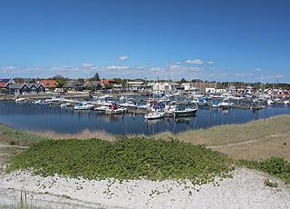 Der gemütliche Hafen mit Segel- und Fischerbooten hinter den Dünen in Hou