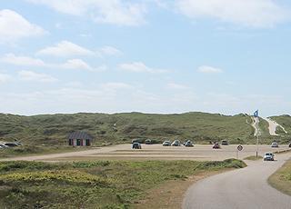 Parkeringsplads og blåt flag bag de høje klitter ved Houstrup Strand