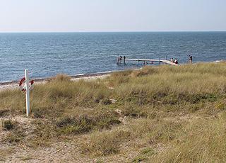 Strand med badebro foran klitterne i Hummingen
