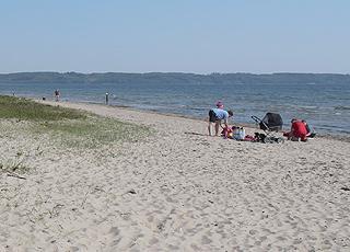 Familie på sandstranden i ferieområdet Hvidbjerg