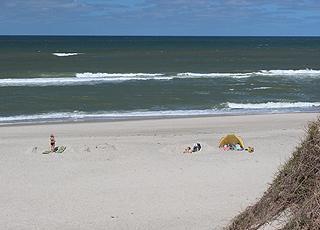 En sommerdag med badegæster på stranden i Klegod