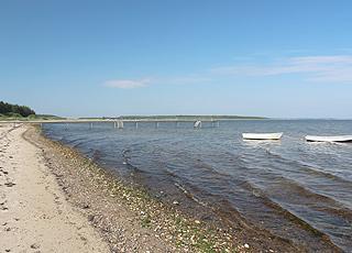 Kleine Boote auf dem Wasser vor dem Strand und dem Ferienhausgebiet Lihme