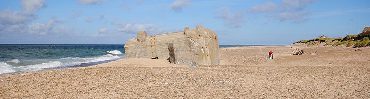 Sandstrand med bunker, klitter og sommerhuse med havudsigt