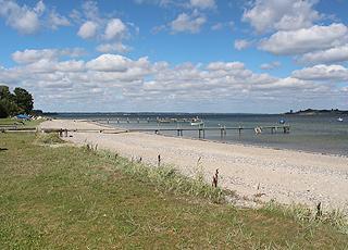 Bred sandstrand med flere badebroer i ferieområdet Loddenhøj