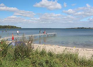 Lang badebro ved stranden med det klare vand i ferieområdet Løjt