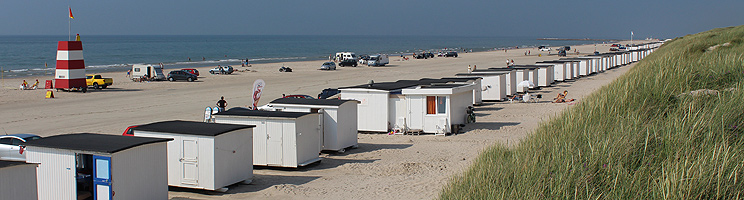A summer day at the beach of Løkken with lifeguard tower and the characteristic white beach houses