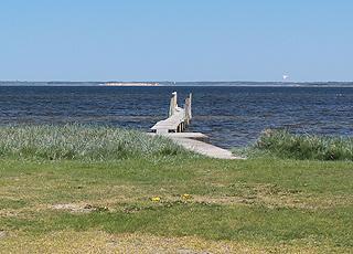 Badebro ved de grønne områder bag stranden i Lundø