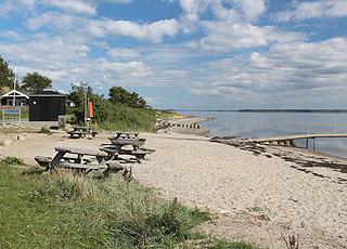 Der  schöne Sandstrand mit Badesteg, direkt bei den Ferienhäusern in Lyby Strand