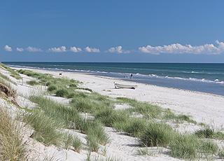 Sandschloss aus feinem weißen Sand am Rand des Wassers am Lyngså Strand