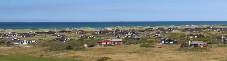 Ferienhäuser in grüner Umgebung hinter den hohen Dünen bei Nørlev Strand
