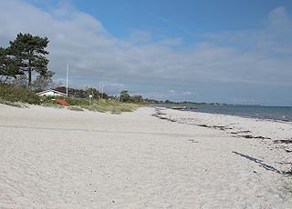 Den brede sandstrand og sommerhuse langs kysten i Saksild