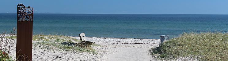 Kunstværk og bænk ved Saksilds dejlige sandstrand med lavt, klart vand